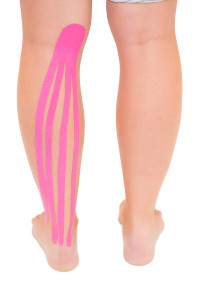 Patients leg with applied kinesio tape on white background